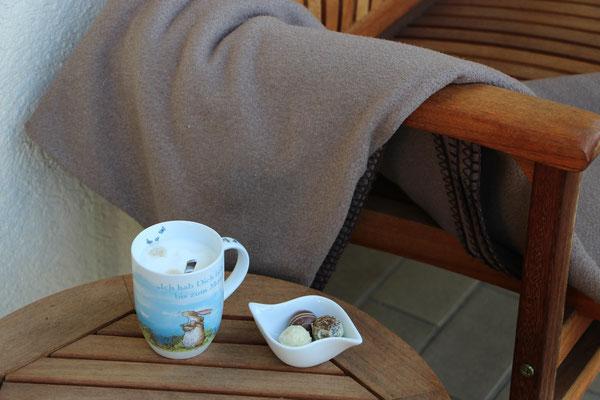 Ein Tasse Kaffee, Trüffel-Pralinen und eine Decke auf unserer Balkon-Bank