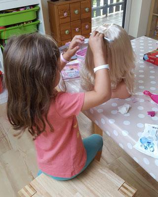 Unsere Kleine frisiert ihre Schminkpupppe