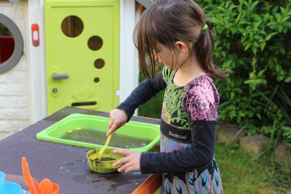 Unsere Große spielt an der selbstgebauten Matschküche im Garten