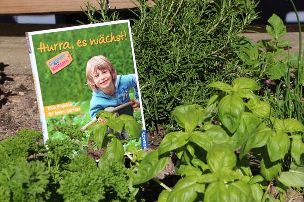 """Das Buch """"Hurra, es wächst"""" inmitten des Kräuterbeets"""