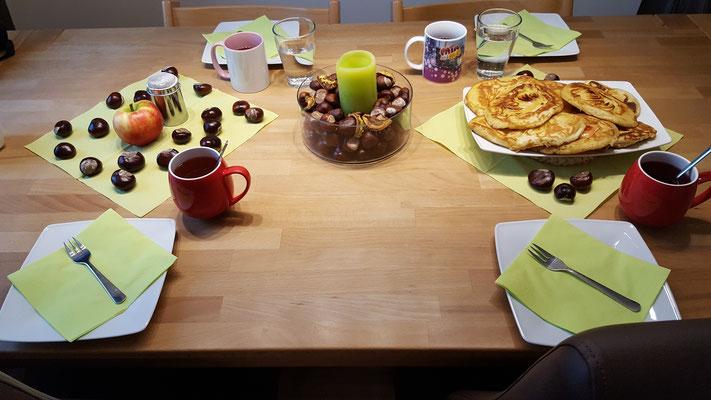 Der gedeckte Kaffeetisch - mit Apfel-Pfannkuchen, Tee und Kastanien