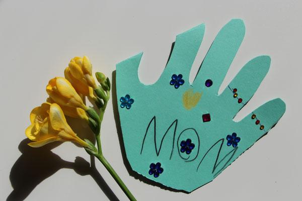 Muttertagskarte einer Hand, welche auseinandergefaltet ein Herz darstellt