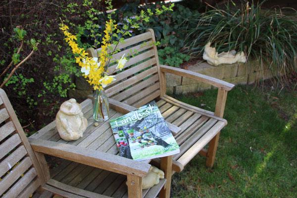 """Die Zeitschrift """"Landlust"""" auf unserer Gartenbank mit Dekofrosch und Blumen"""