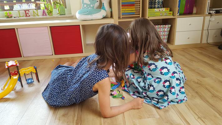 Unsere Mädels vor einer von drei großen Kisten voll mit Playmobil