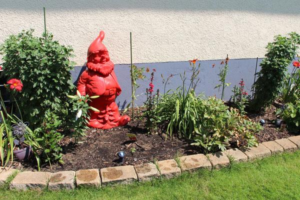 Unser Hausbeet mit roten Chrysanthem, Sonnenbraut, Lilien und Gartenzwerg