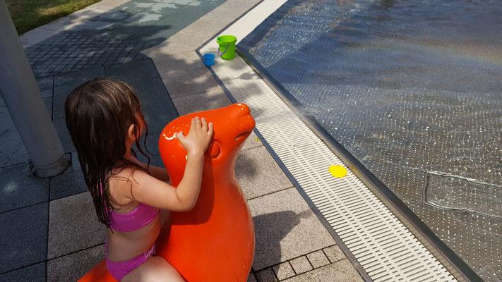 Unsere Kleine auf einem wasserspeienden Seehund im Kinderbecken des Rebstockbad Frankfurt