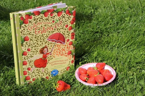 """Das Buch """"Erdbeerinchen Erdbeerfee - Sonnenschein und Erdbeerzauber"""" mit einer Schale voll Erdbeeren"""