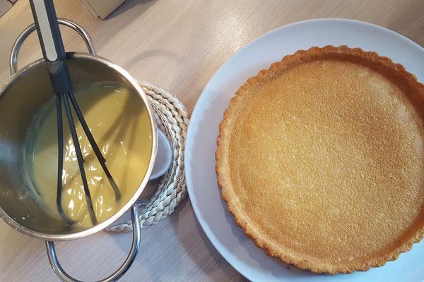 Ein Topf mit Vanillepudding und ein Teller mit einem fertigen Tortenboden