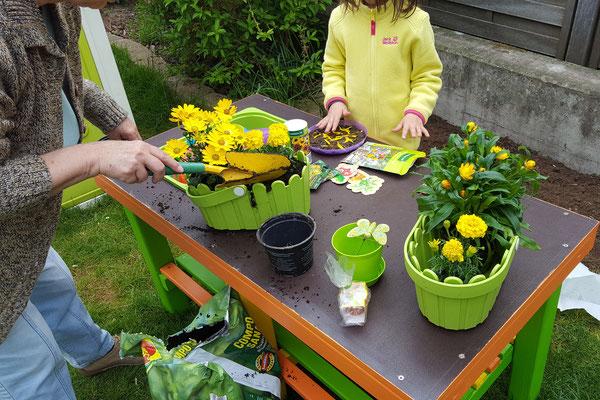 Oma und die Große bepflanzen auf der Matschküche Blumentöpfe für die Kinderecke