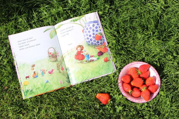 """Das aufgeschlagene Buch """"Erdbeerinchen Erdbeerfee - Im Erdbeergarten ist was los"""" mit eine Schale voll Erdbeeren"""