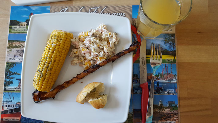 gegrillter Mais, Reissalat und eine Grillfackel auf dem Teller