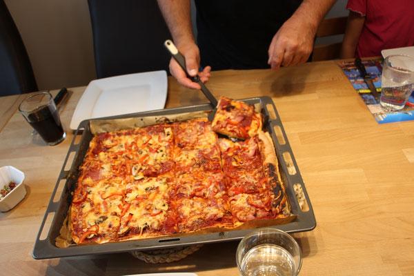 Stefan serviert die fertige Pizza
