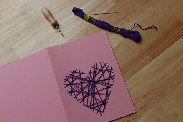 Faden wird durch die Löcher gefädelt, so dass sich das Herz mit Fäden füllt