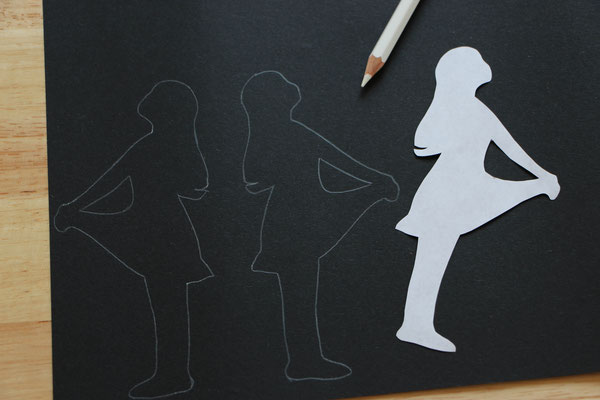 Sterntaler-Figur auf schwarzes Tonpapier gezeichnet