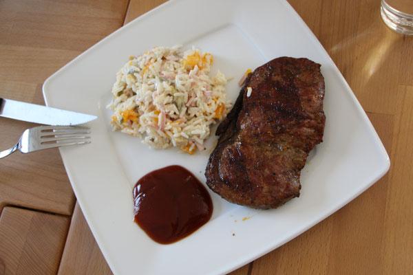Reissalat und Grillfleisch auf dem Teller