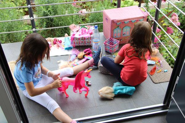 Unsere Mädels spielen auf der Eingangstreppe mit ihren Barbies