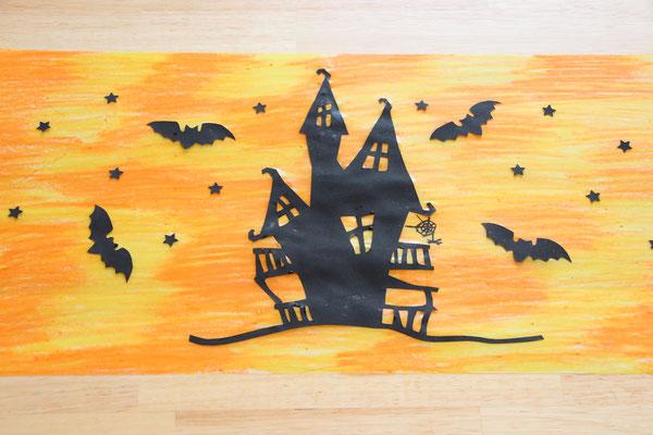 das Hexenhäuschen, die Feldermäuse und Sterne aus schwarzem Tonpapier; aufgeklebt auf dem orange-gelben Laternen-Transparentpapier