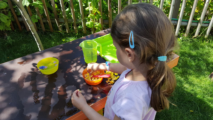 Unsere Kleine bereitet an unserer Matschküche diversen Rosenblätter-Gerichte zu
