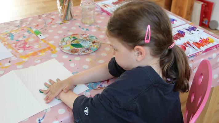 Unsere Kleine macht einen Handabdruck auf die Karten