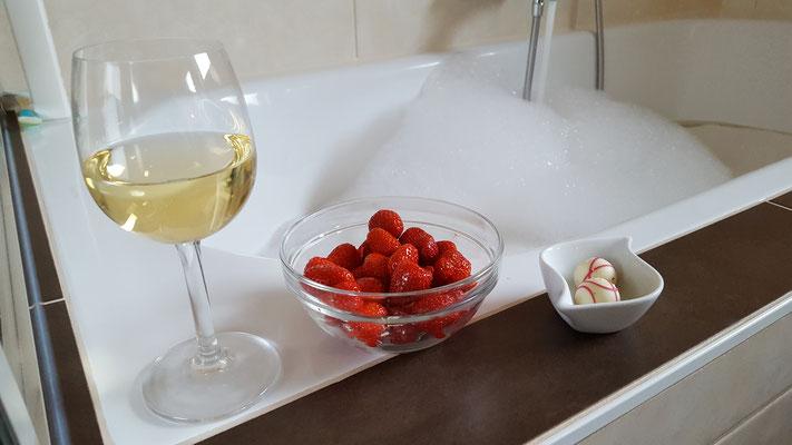 Ein Glas Weißwein, Erdbeeren und Trüffelpralinien bei einem eingelassenen Bad