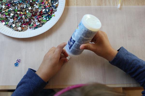 Unsere Kleine klebt Glitzersteine auf das Laternen-Transparentpapier