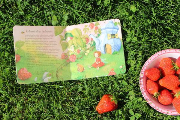 """Das afugeschlagene Buch """"Erdbeerinchen Erdbeerfee - Du bist die Beste!"""" mit einer Schale voll Erdbeeren"""