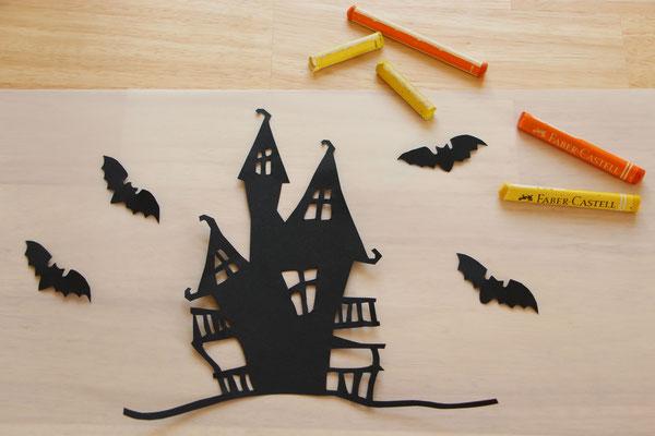 das aus schwarzem Tonpapier ausgeschnittene Hexenhäuschen, Laternen-Transparentpapier, Wachsmalstifte in gelb und orange
