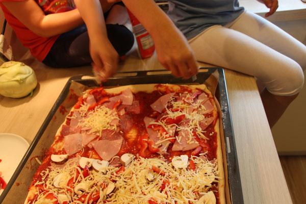Die Mädels belegen sich ihre Pizzastücke