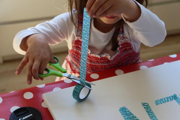 Unsere Kleine schneidet Tape für ein Kunstwerk