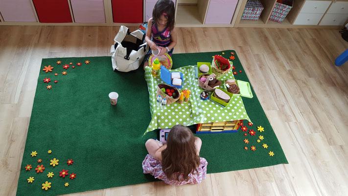 """Die Mädels spielen """"Picknick"""" im Kinderzimmer auf einer großen Blumenwiese"""