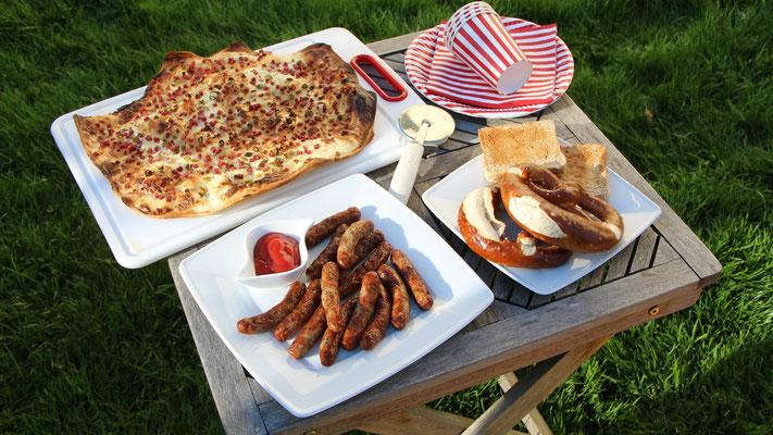 Ein kleiner Tisch mit Flammkuchen, kleinen Rostbratwürsten, Brezeln und Toastbrot