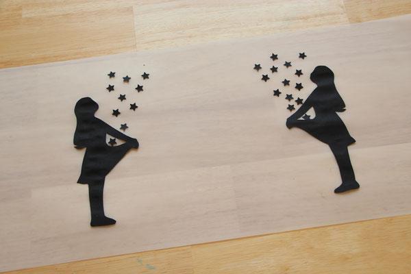 die schwarzen Sterntaler-Figuren und Sterne auf das Laternen-Transparentpapier geklebt