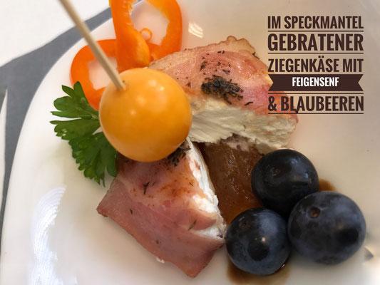 Fingerfood auf kleinem Eventgeschirr mit Schafskäse im Speckmantel und Blaubeeren