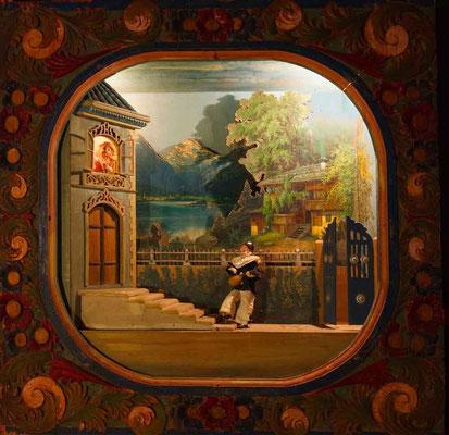 """Automatenszene aus dem XIX. Jahrhundert: ein junger """"Pierrot"""" oder ein """"Pulcinella/Polichinelle"""" spielt für das junge Mädchen am Fenster /Im Hintergrund Hallstatt"""