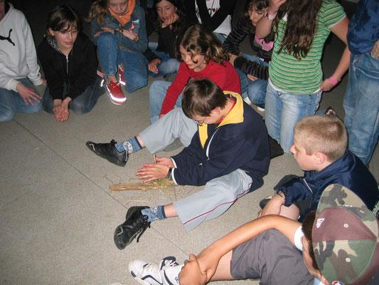 Au centre d'accueil un groupe pratique l'activité découverte du feu à la préhistoire