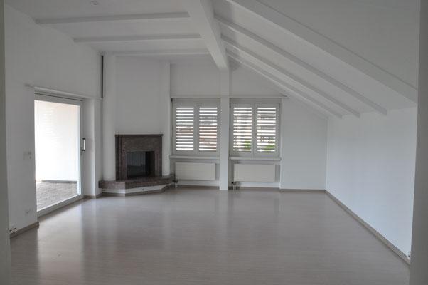 Wohnzimmer mit Cheminée und Ausgang zum Balkon
