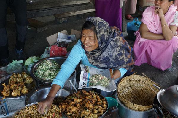 Die Marktfrau richtet das bestellte Essen...