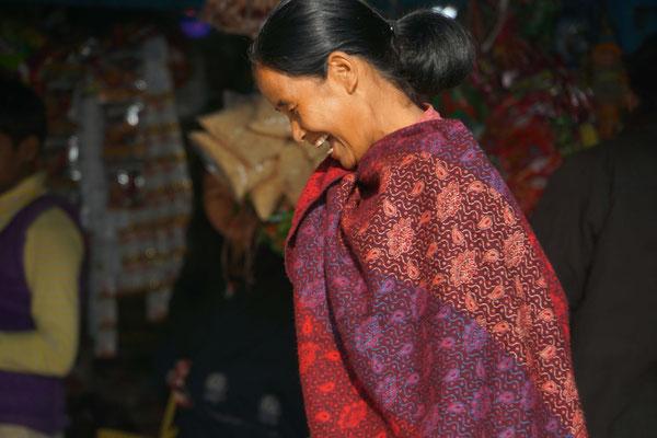 Die Marktfrau verlegen lachend...