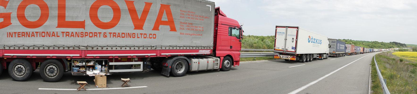 """Ein Versuch, die laaaaange Kolonne der wartenden LKWs einzufangen. Beim Camion ganz links seht ihr auch die """"Küchenzeile"""", die sie mitführen..."""