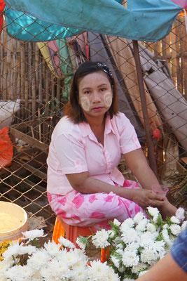 Blumenverkäuferin mit traditioneller Gesichtsbemalung...