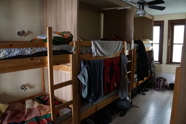 Im mittleren Bett unten wohne ich. Der Gummizug, mit welchem ich das Zelt am Velo befestige, dient mir als Vorhangschiene. Alles kann trocknen und ich gewinne gleichzeitig etwas Privatsphäre - nicht schlecht für 10 Euro inkl. Halbpension - oder??!!