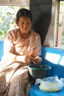 Im Zug rüstet die Bäuerin Bohnen, die sie dann in Yangon auf dem Markt verkaufen will - bei uns arbeitet man im Zug auch - aber meist am Laptop...