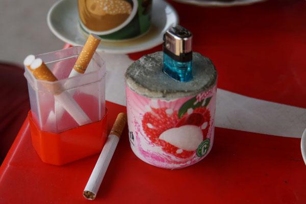 Zigaretten werden in den Restaurants offen/einzeln verkauft - und das Feuerzeug wird schon mal in einer alten Getränkeflasche in Beton gegossen, damit es bleibt, wo es hingehört...