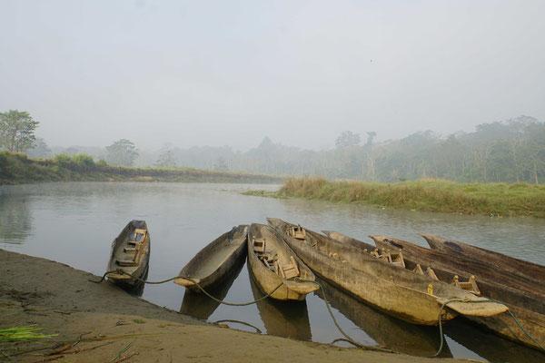 Die Kanus liegen am frühen Morgen auf dem stillen Wasser des Flusses...