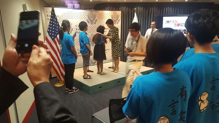 米国ワシントンDCの日米協会主催のジャパンボウルの優勝者訪日イベントで記念メダルを授与されている高円宮妃殿下(Princess Takamadonomiya presenting a memorial medal to the winner team members of the Japan Bowl conducted by Japan America Society of Washington, DC.)