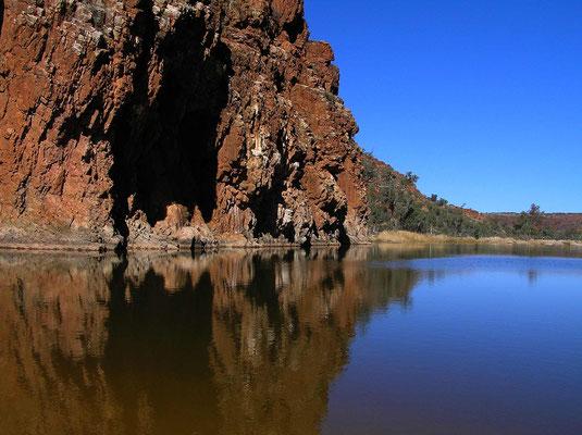 Für die Arandastämme ist das tiefe Wasserloch die Heimat der Riesenwasserschlange.