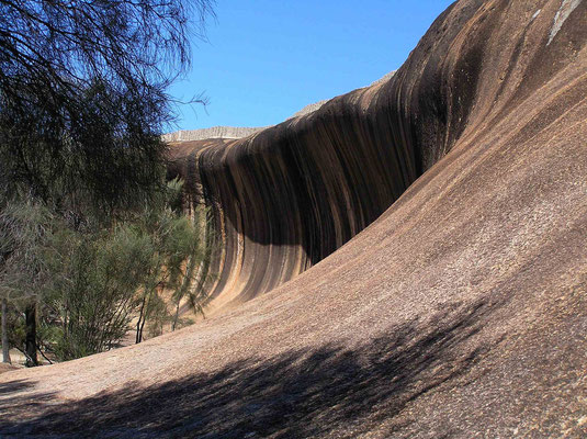 Verschiedene chemische Prozesse bei der Beruehrung mit Wasser gestalteten die den Wave Rock charakterisierenden vertikalen Streifen. Ausgewaschene Karbonate bilden die schwarzen, Eisenhydroxid die roten Streifen.
