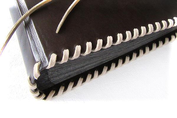 Lederalbum antik-dunkelbraun mit umlaufender Schnürung in hellbeigen Velour-Flachband und schwarzen Innenseiten mit Pergaminzwischenblättern