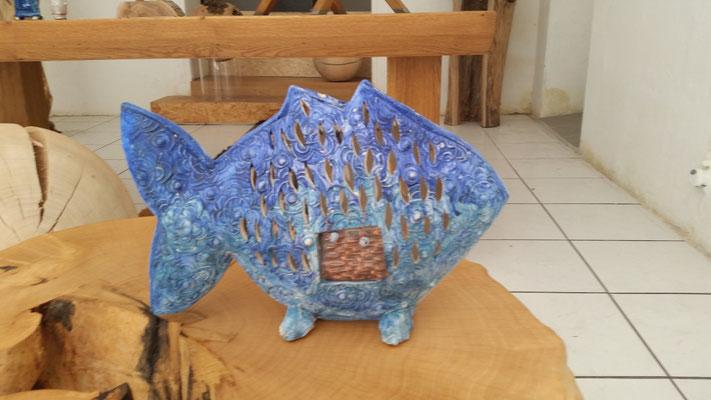 ein Fisch(Windlicht) inmitten von Möbel und Klavierkunst von Andi Berner