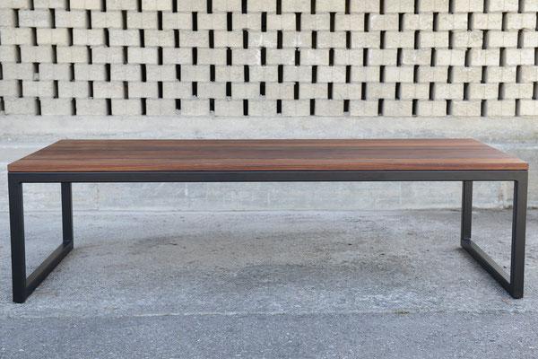 Tischplatte aus Holz vor einer gemauerten Wand